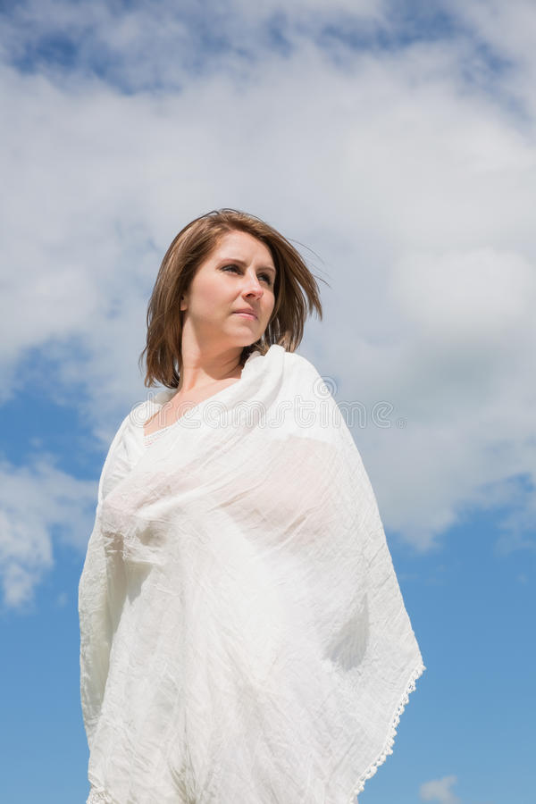 Woman looking away against blue sky and clouds stock photography