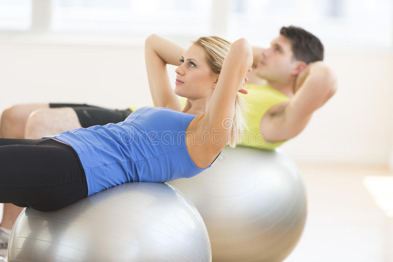 Woman Looking Away While Exercising On Fitness Ball At Gym. Beautiful young women looking away while exercising on fitness ball with men in background at gym royalty free stock photos