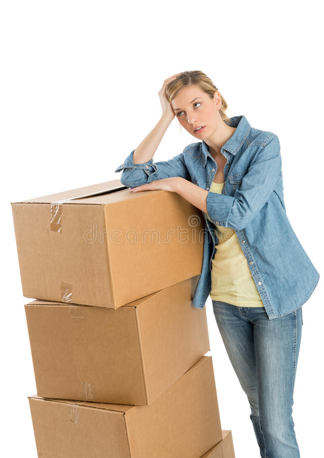 Woman Looking Away While Leaning On Stacked Cardboard Boxes stock photo