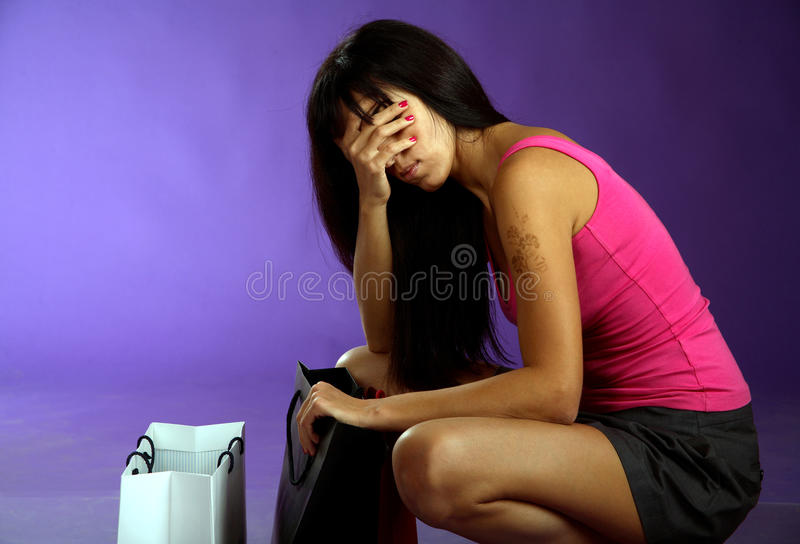 Woman looking at bag and very tired after shopping. Studio, violet background royalty free stock photos