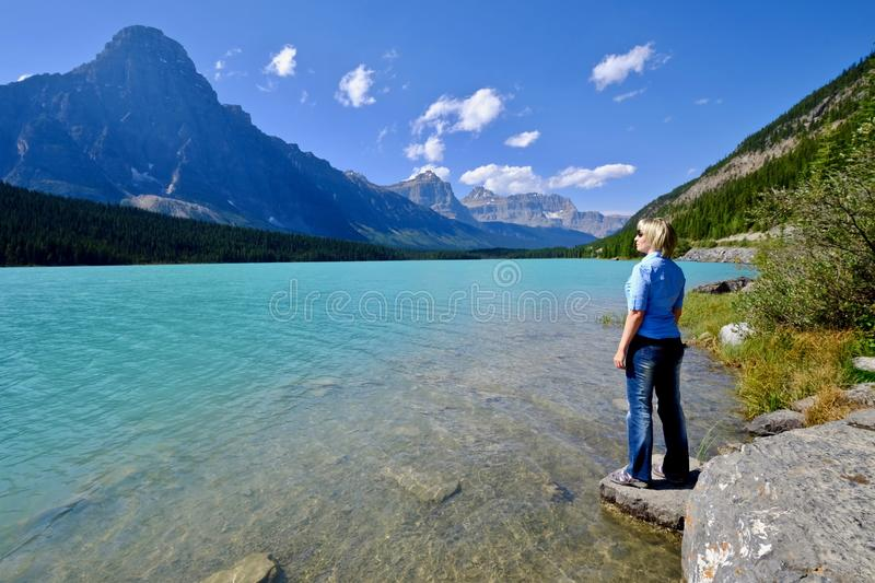 Woman looking at the beautiful view of clear turquoise lake and rocky mountains. royalty free stock photos