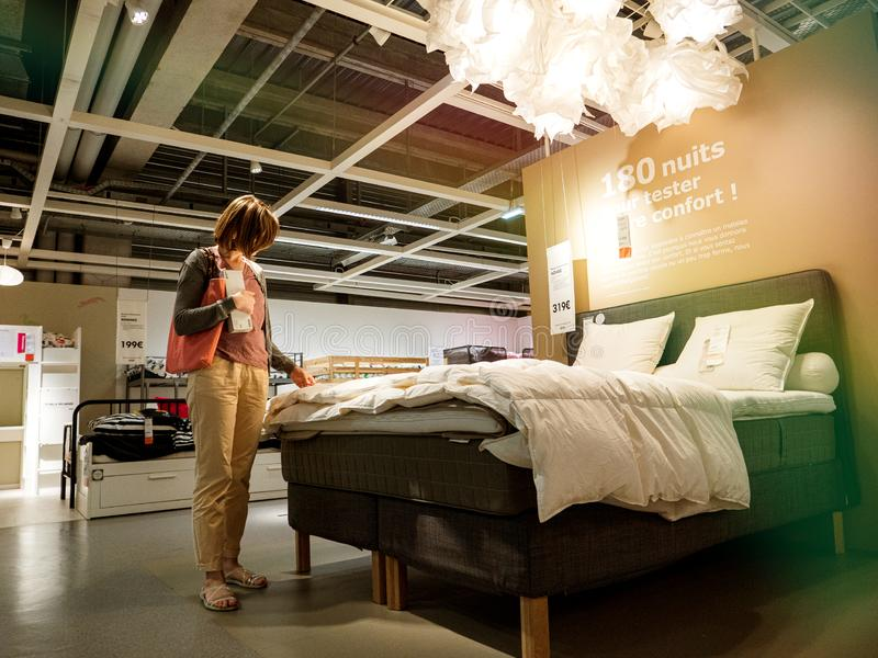 Woman looking at bed duvet choosing bed linen stock images