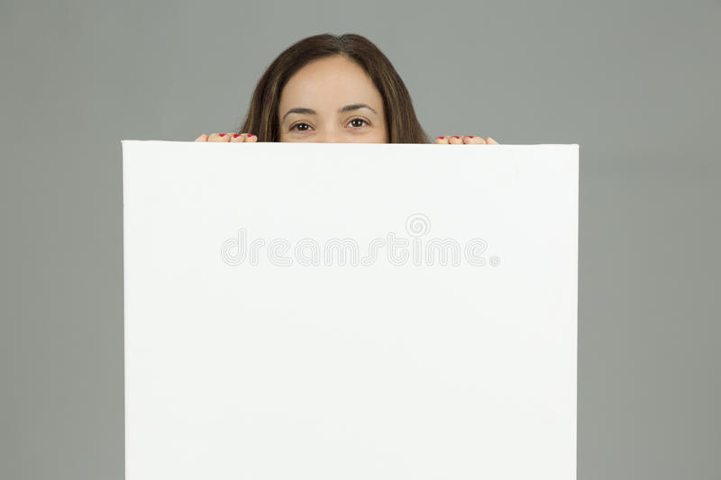 Woman looking from behind a blank advertising board stock photos