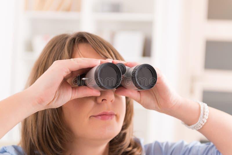 Woman looking through binocular stock photos
