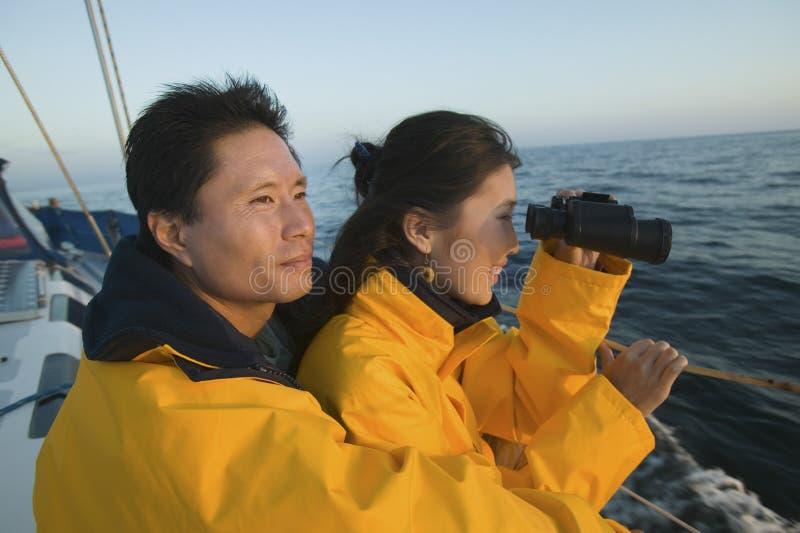 Woman Looking Through Binocular With Man On Yacht stock photos