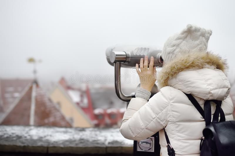 Woman looking through binoculars to the view of Tallinn Old Town on winter day. Romantic view of the snowy roofs of a medieval. Woman looking through binoculars royalty free stock photo