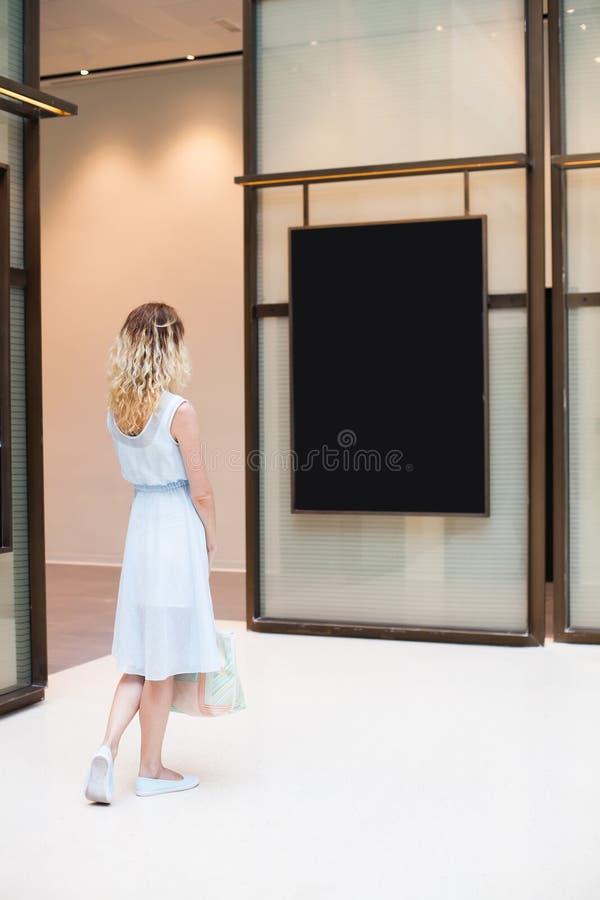 Woman looking at black blank poster royalty free stock photo