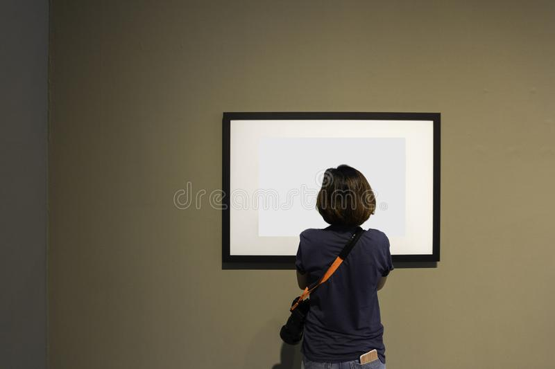 Woman is looking at blank photo frame on wall stock photos