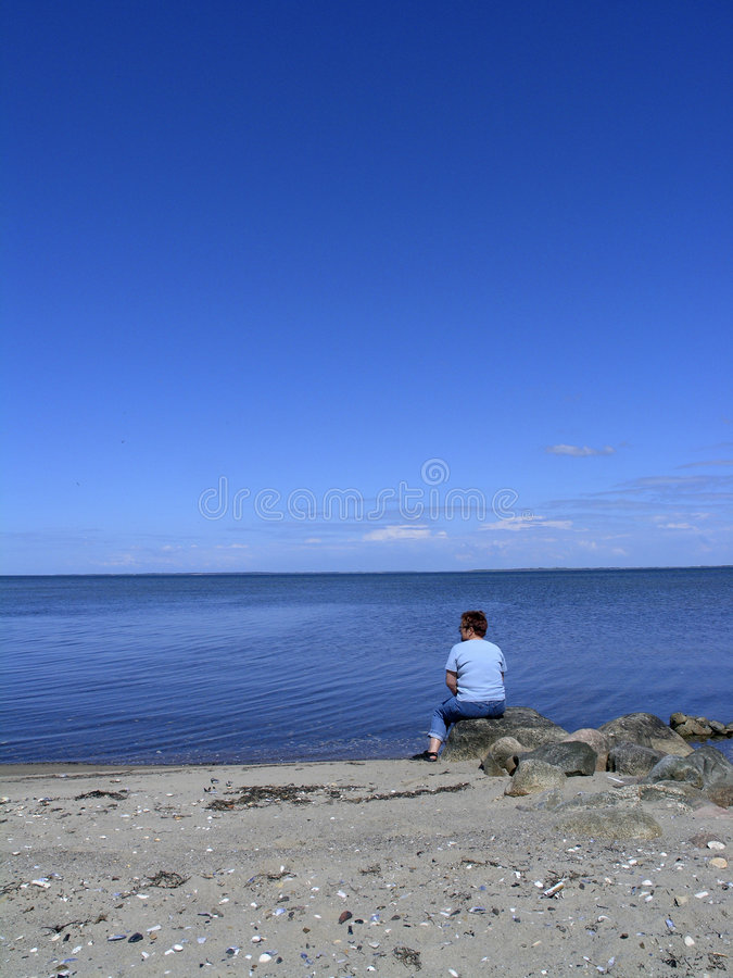 Woman looking at blue sea royalty free stock photo