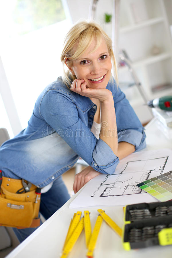 Woman looking at blueprint before beginning works stock photography
