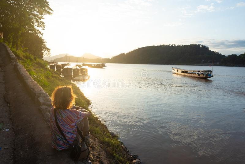 Woman looking at boats on Mekong River at Luang Prabang Laos, sunset dramatic sky, famous travel destination backpacker in South royalty free stock images