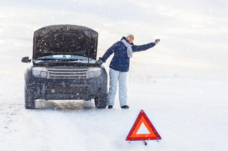 Woman looking on the broken car looking at the motor. Around winter and snow field. stock images
