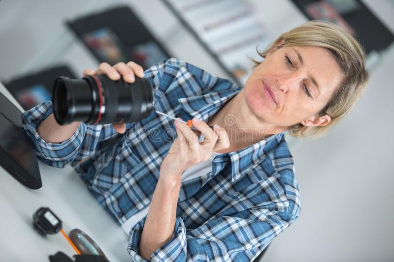 Woman looking at broken photographic lense stock photography