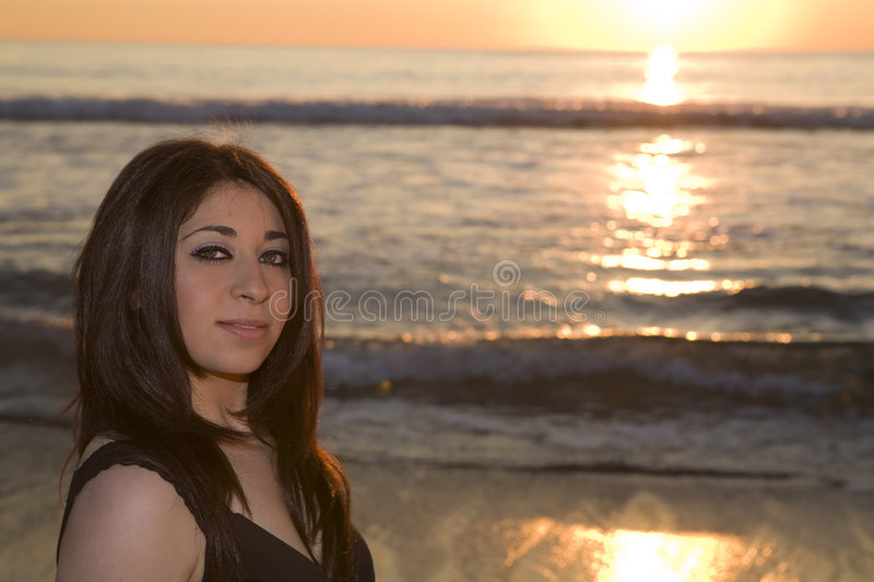 Woman looking at the Camera on the beach at. Young Beautiful Brunette looking at the Camera on the beach at sunset royalty free stock photos