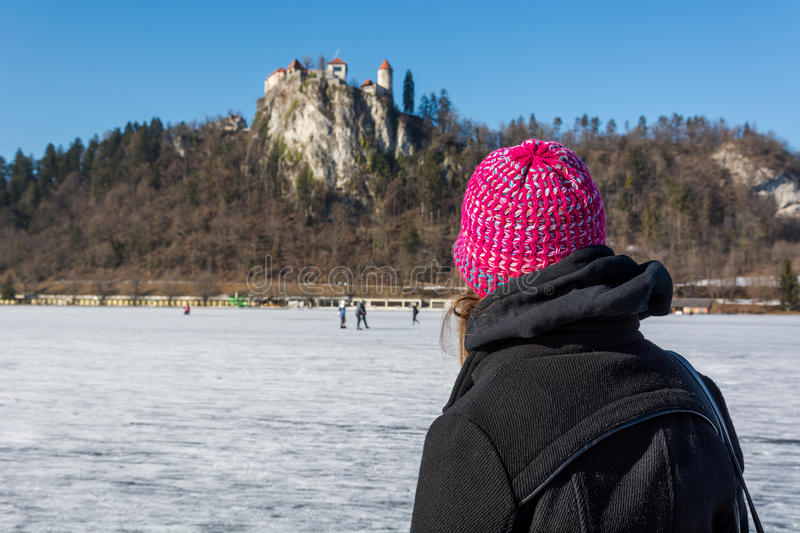 Woman looking at a castle situated on rock. stock photo