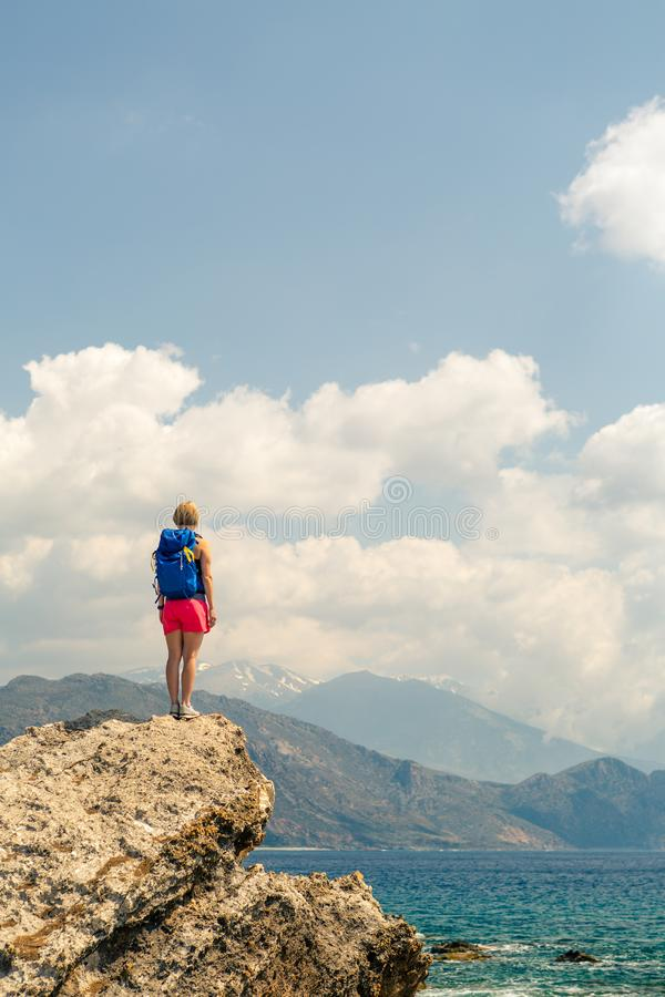 Woman looking and celebrating sunrise and landscape. Woman celebrating or praying in beautiful inspiring mountains sunrise. Girl hiker on mountain top hiking or royalty free stock photo