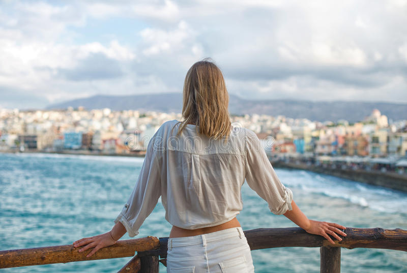 Woman looking at cityscape. Woman looking at cityscape with bay. From the back. Place for your text royalty free stock photo
