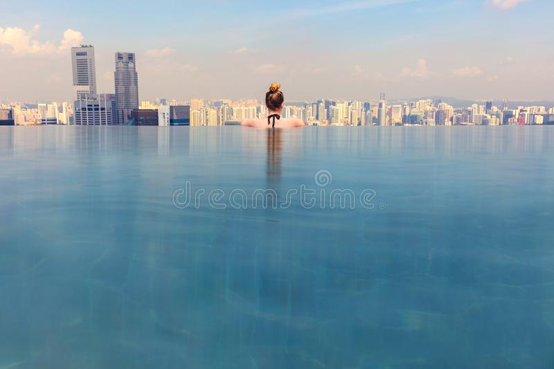 Woman Looking At Cityscape While Relaxing In Infinity Pool. Rear view of woman looking at cityscape while relaxing in the hotel roof top infinity pool stock image
