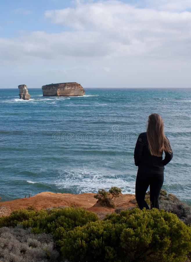 A woman looking at the cliffs in the Bay of Islands area at the Great Ocean Road in Australia royalty free stock image