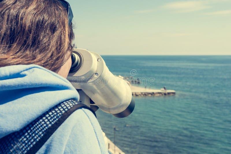 Woman looking through coin operated binoculars at seaside. stock photo