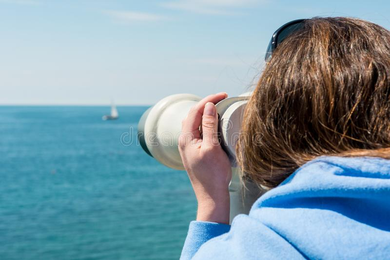 Woman looking through coin operated binoculars at seaside. royalty free stock images