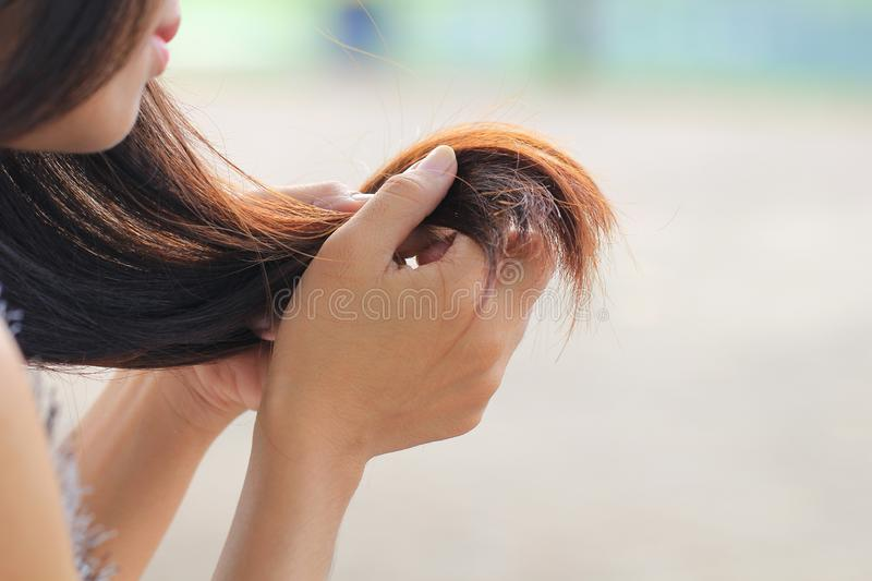 Woman looking at damaged splitting ends of hair, Haircare concept royalty free stock photos