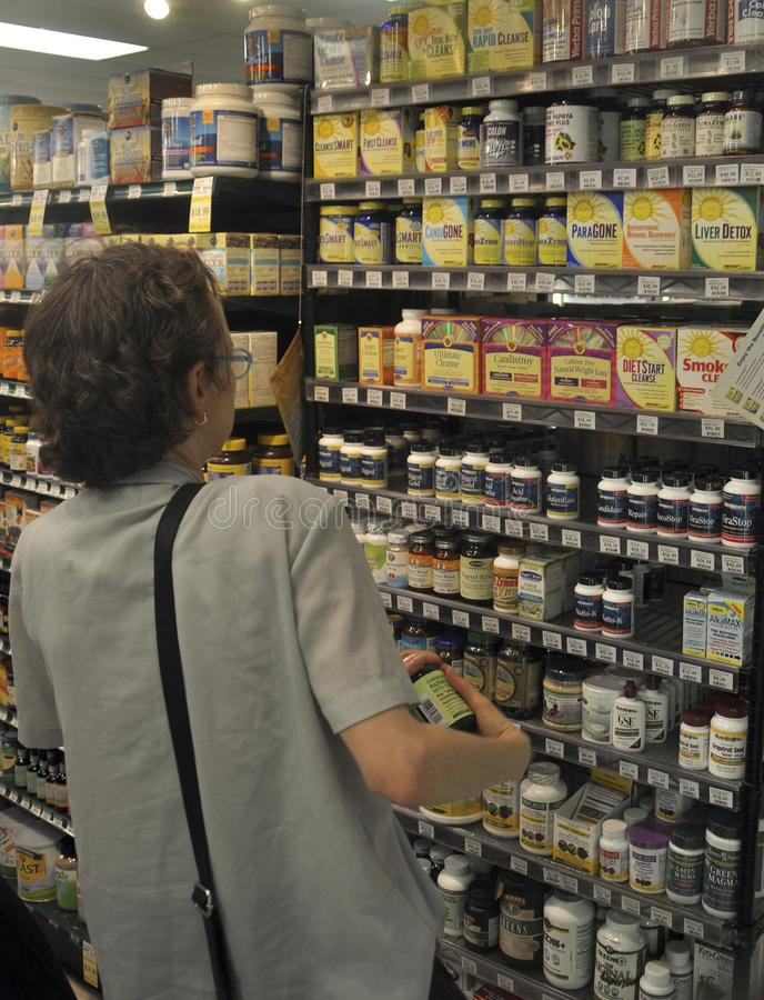 A woman searches for vitamins at the health food store in College Park, Maryland stock image