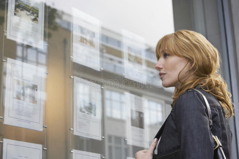 Woman Looking At Display At Real Estate Office. Side view of a young women looking at window display at real estate office royalty free stock image