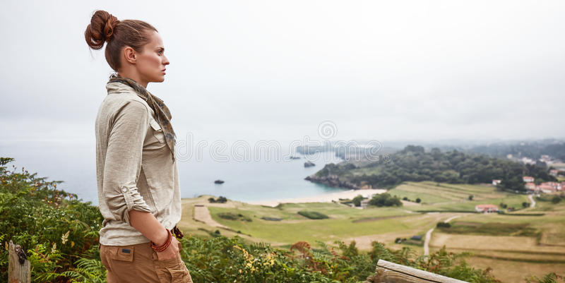 Woman looking into distance in front of ocean view landscape. Into the wild in Spain. active woman hiker looking into the distance while standing in the front of royalty free stock photography