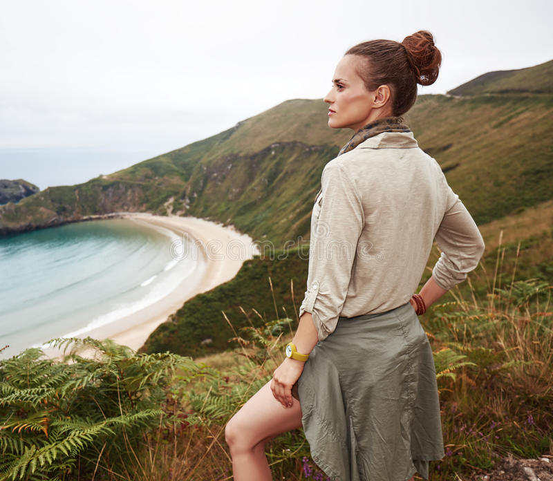 Woman looking into distance in front of ocean view landscape. Into the wild in Spain. adventure woman hiker looking into the distance in front of ocean view stock photos