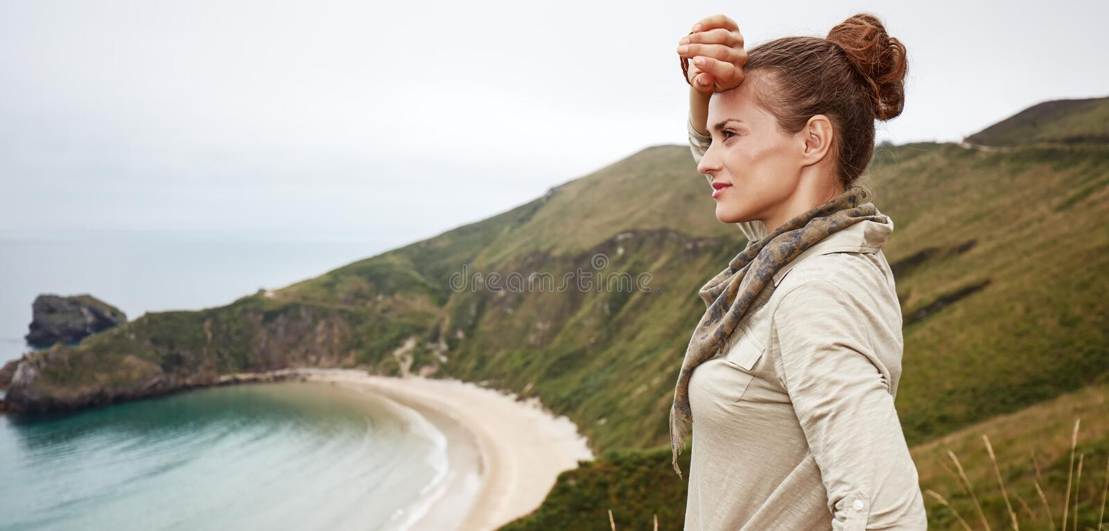 Woman looking into distance in front of ocean view landscape. Into the wild in Spain. Portrait of adventure woman hiker looking into the distance in front of royalty free stock image