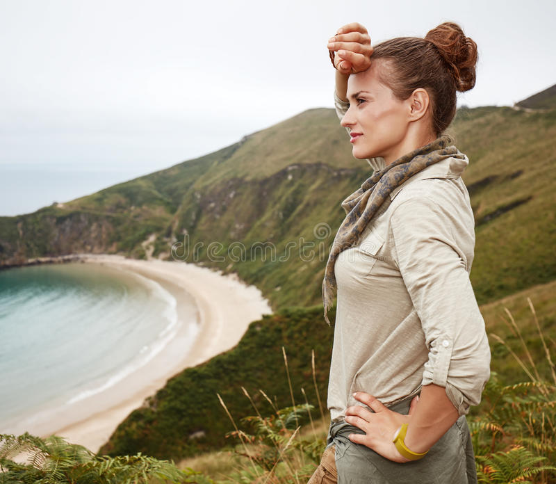 Woman looking into distance in front of ocean view landscape. Into the wild in Spain. Portrait of adventure woman hiker looking into the distance in front of royalty free stock photos