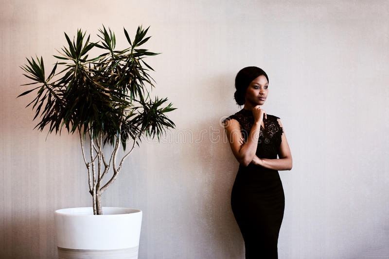 Woman looking into distance thoughtfully while standing next to tree. Young African woman wearing a stunning black dress while looking off camera in thought stock image