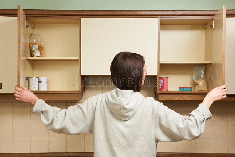Woman Looking In Empty Food Cupboards. Woman Looks In Empty Food Cupboards stock image