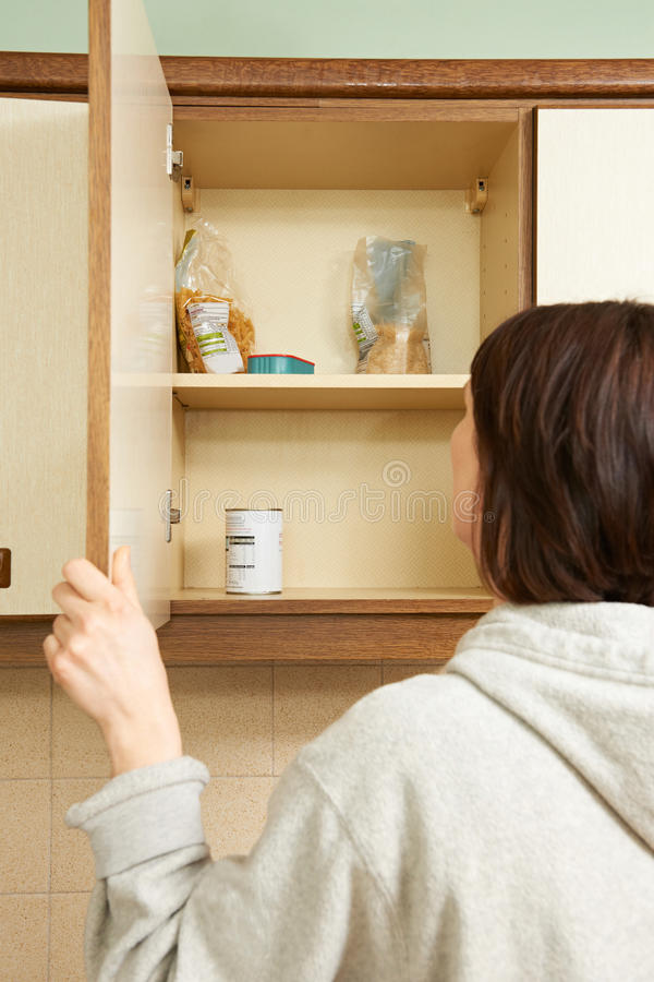 Woman Looking In Empty Food Cupboards. Woman Looks In Empty Food Cupboards stock images