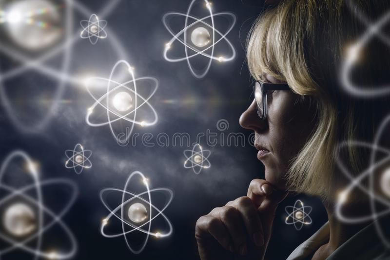 Woman looking explores atoms . royalty free stock images