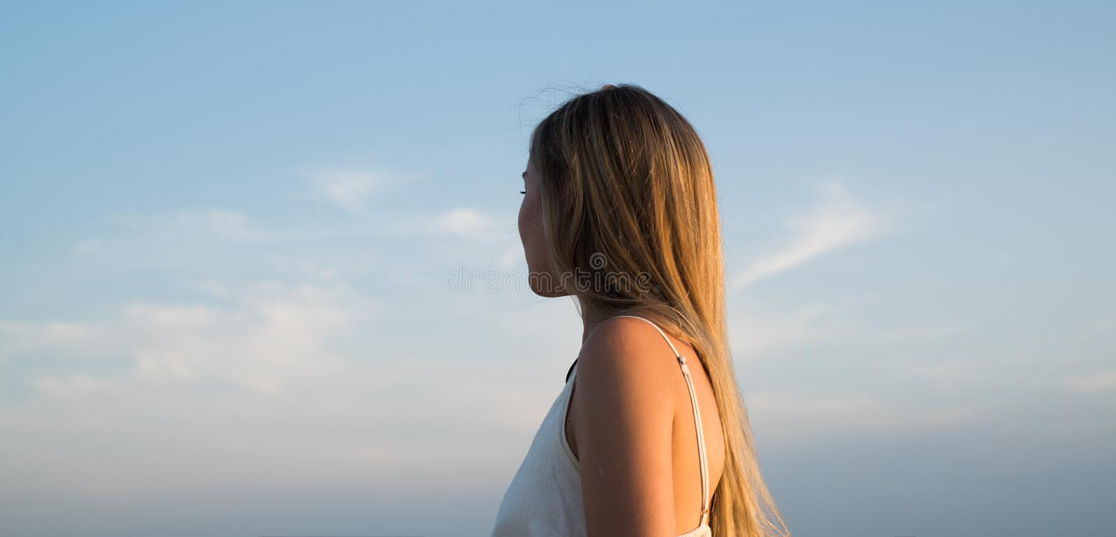 Woman looking far away. dreaming about better times. success. future life. traveling concept. girl on sunset sky royalty free stock photography
