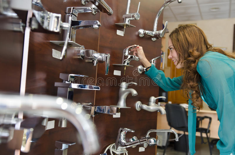 Woman looking faucets at store stock photography