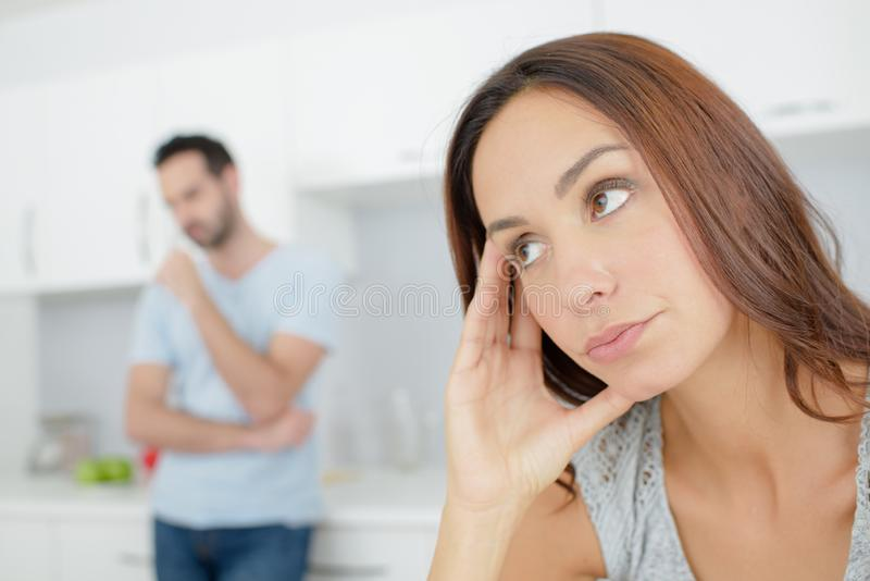 Woman looking fed up partner in background stock photography