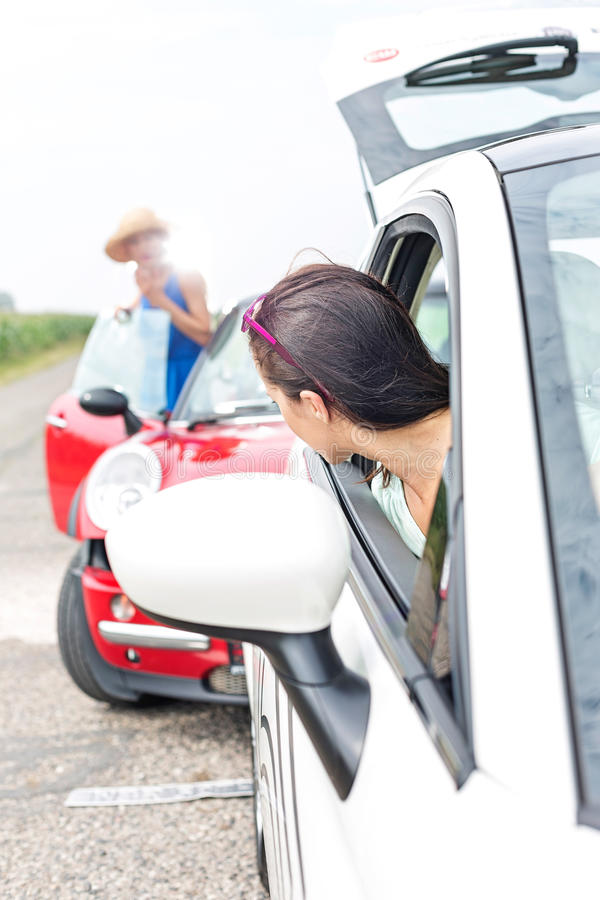 Woman looking at female crashing car on road stock photos