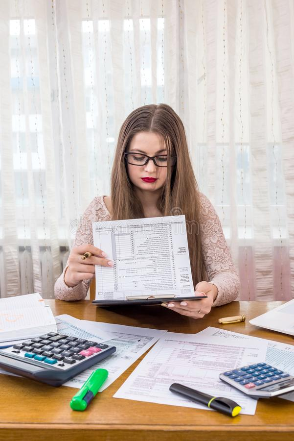 Woman looking through 1040 form preparing to fill.  royalty free stock photography