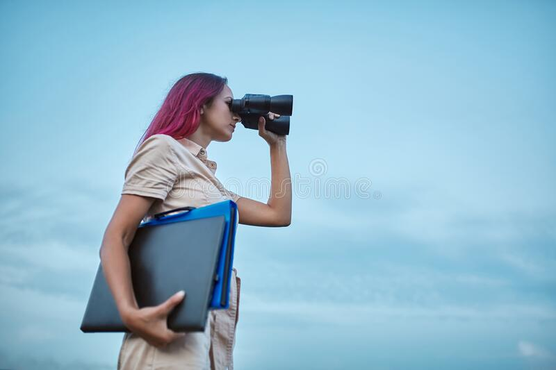 Woman looking forward in binoculars. Lady holding laptop and folder. Goal setting and new horizons concept, copy space.  royalty free stock images