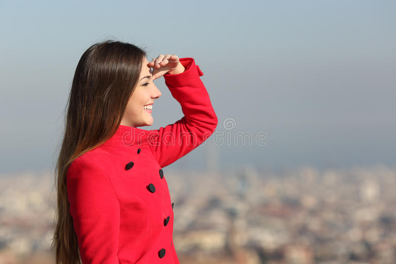 Woman looking forward with city in the background. Woman looking forward in winter with a red coat with city in the background stock images