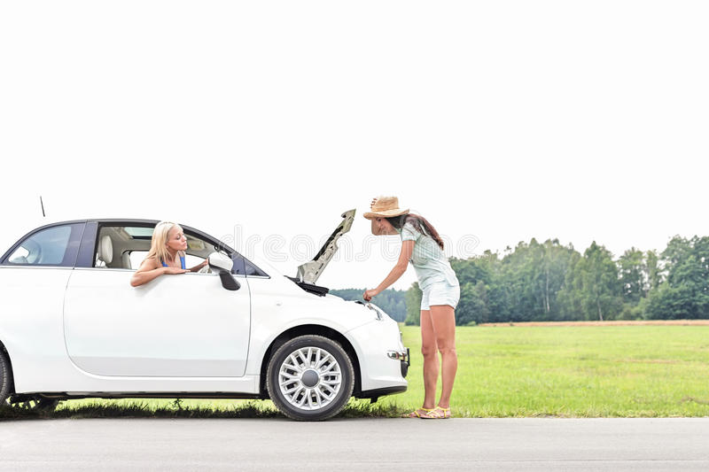 Woman looking at friend repairing broken down car on country road royalty free stock photography