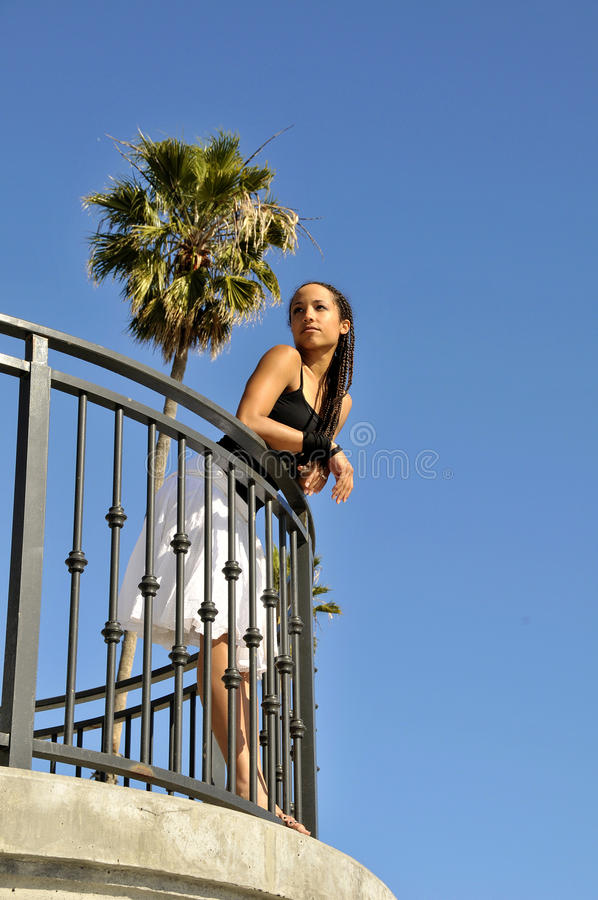 Woman Looking Gazing Off In Distance From Balcony Stock