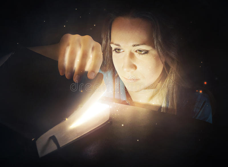 Woman looking into glowing Bible. stock photo