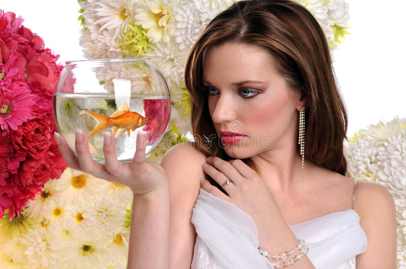 Woman Looking at Goldfish in a Bowl royalty free stock images