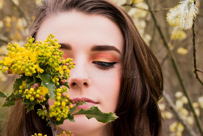 Woman Looking at a Green and Yellow Leafed Plant stock photos