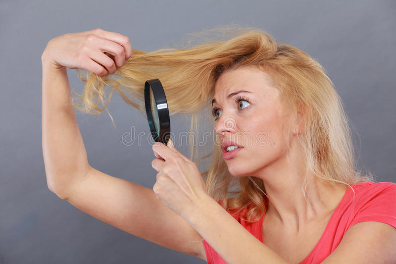 Woman looking at hair through magnifying glass stock images