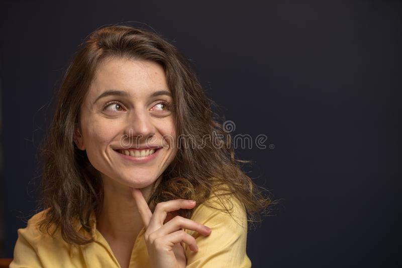 Woman looking up with happy expresison. Woman looking happy with hand on chin in yellow shirt with dark blue walls royalty free stock photos